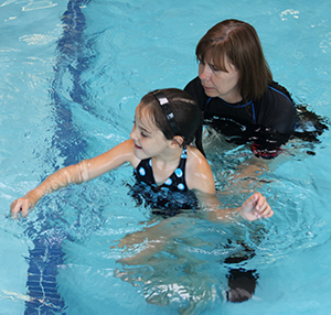 Camee receiving aquatic therapy with Ginny Girten, Marianjoy physical therapist.